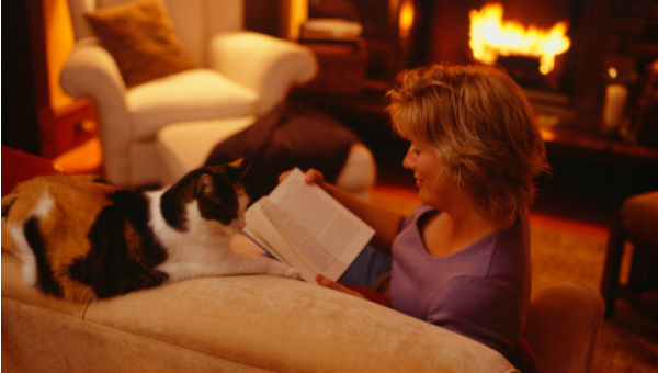 woman reading book in front of fire with cat looming